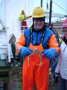 Mann i oljehyre holder krabbe