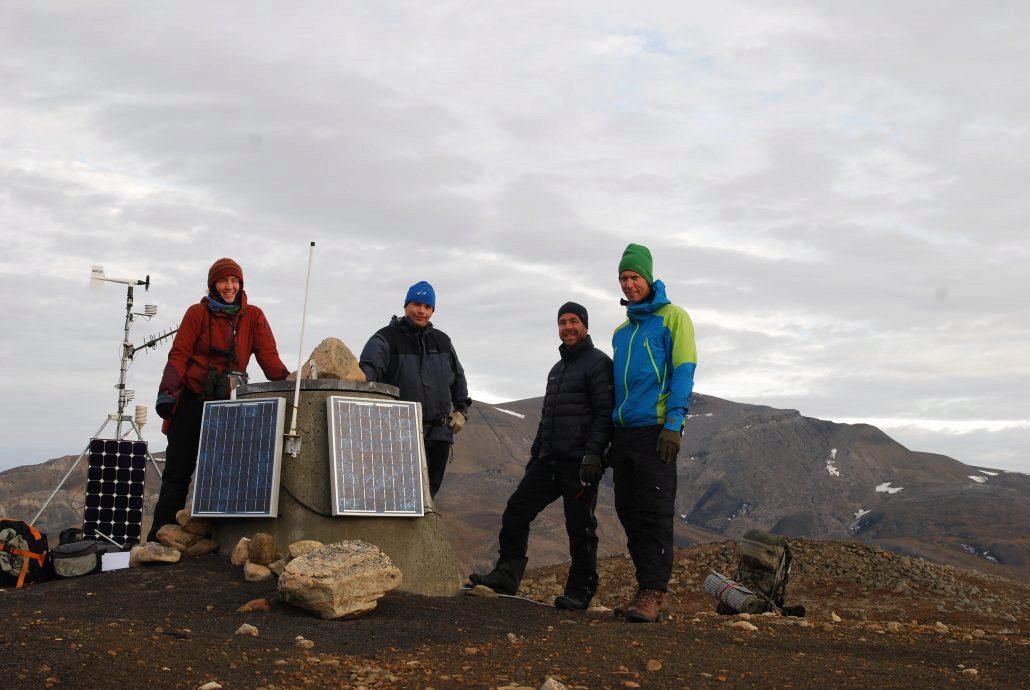 fire personer poserer foran et instrument på en fjellknaus