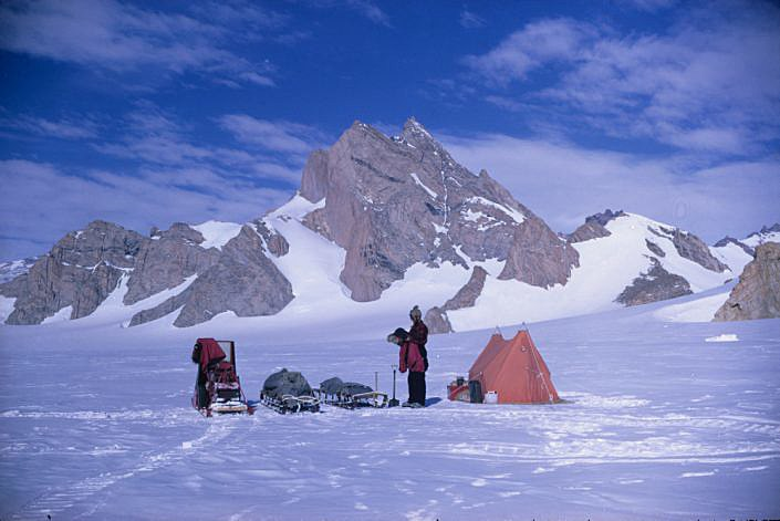 Telt og utstyr foran snedekket fjell