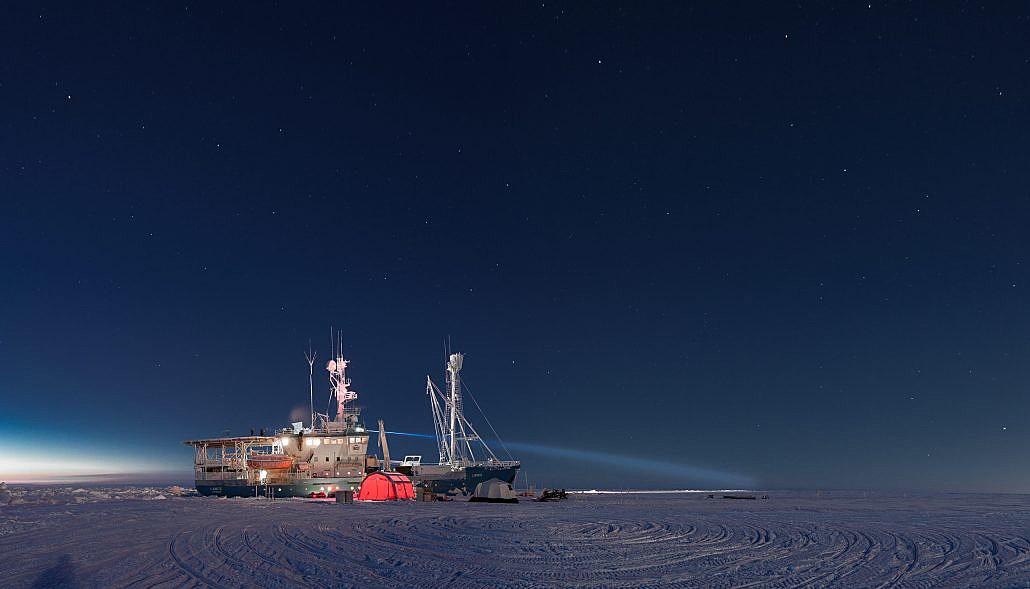 Båt på is i mørketid med forskningstelt og utstyr på isen