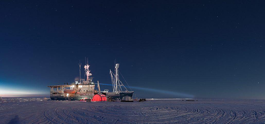 Fartøy på is i mørketid med forskningstelt og utstyr på isen