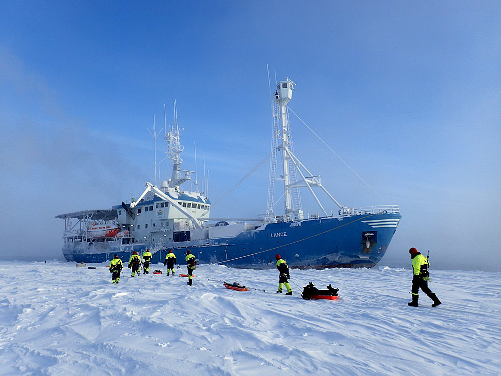 Skip i isen med mennesker i kjeledress rundtomkring