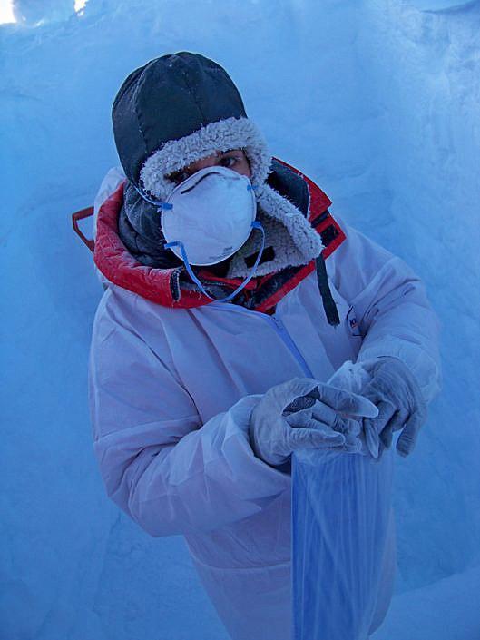 Kvinne i hvit drakt og munnbind nede i snø