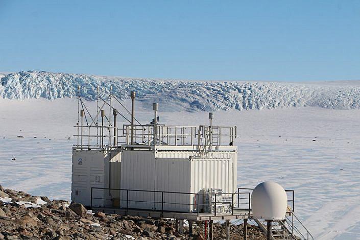 Container med antenner på snedekt fjell