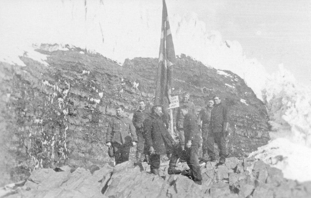 Syv menn står tundt et skilt i en steinrøys