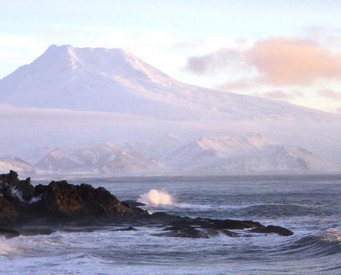 stein i fjæra med vulkanfjell i bakgrunnen
