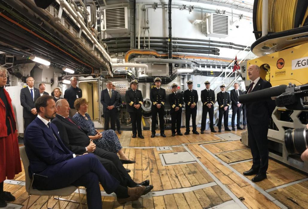 De kongelige sitter om bord og lytter til direktør Misunds informasjon om skipet