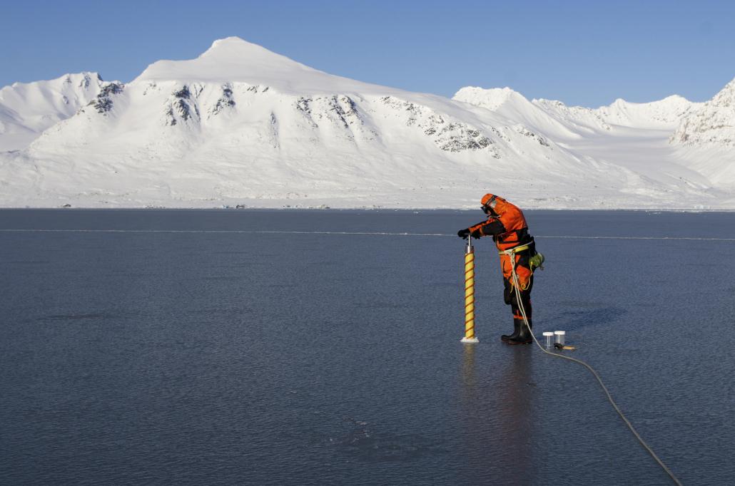 Mann borer på tynn havis