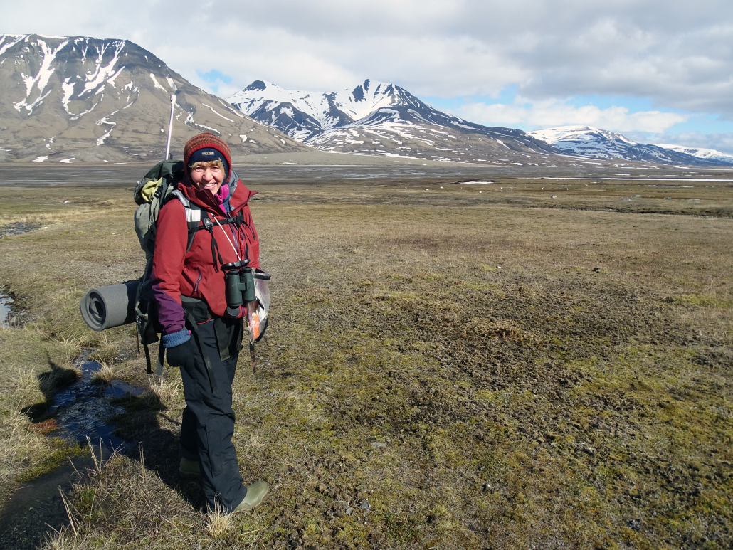 Kvinne står på marka i Svalbards natur, fjell og grønne sletter i omgivelsene