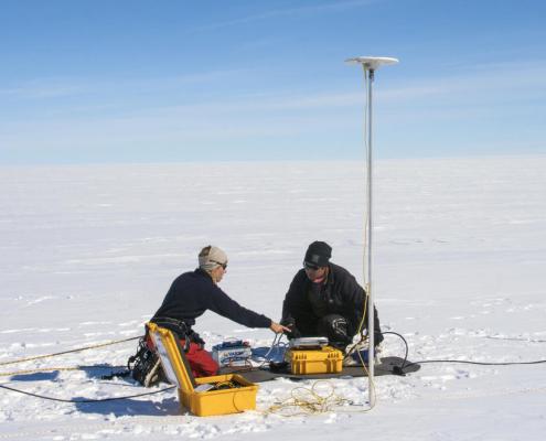 to personer sitter på snø med utstyr