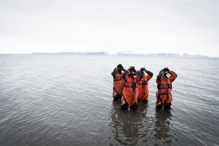 fire personer i overlevelsesdrakt titter i været med kikkert