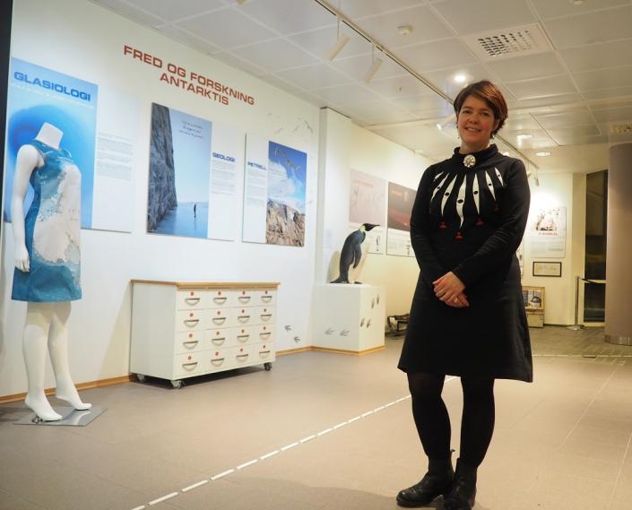 kvinne står foran en utstilling