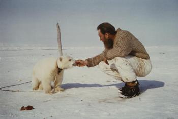 Mann sitter på huk og mater en isbjørnunge i band