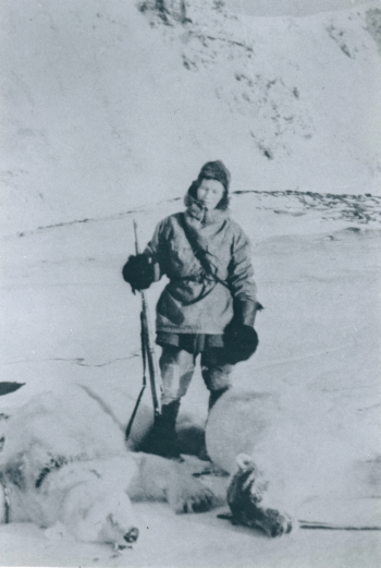 Woman with rifle posing with two dead polar bears.