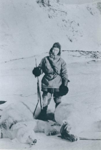 Kvinne med rifle poserer foran en død isbjørn.