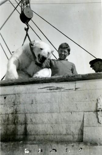 Gutt poserer ned isbjørn som henger med bånd rund halsen på en skip.