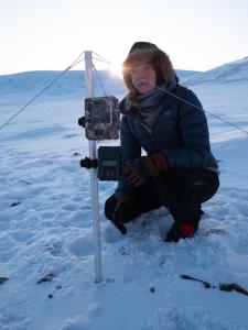 kvinne sitte rpå huk i snø med måleinstrument