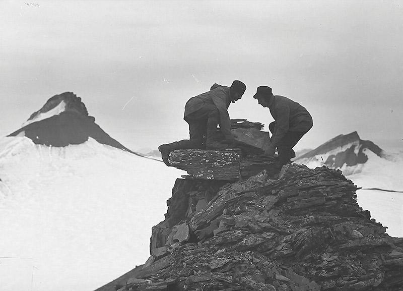 to menn bygger varde på snekledd fjell
