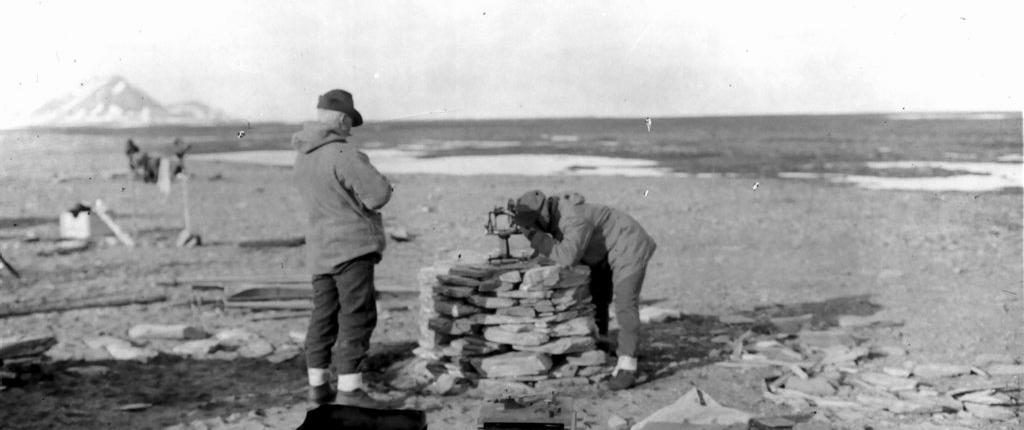to menn foretar målinger på en steinvarde
