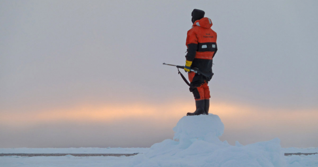 person i oransje klær holde gevær langs bena. Han står med ryggen til