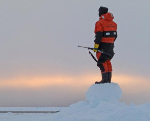 person med gevær i hånda speider utover havet