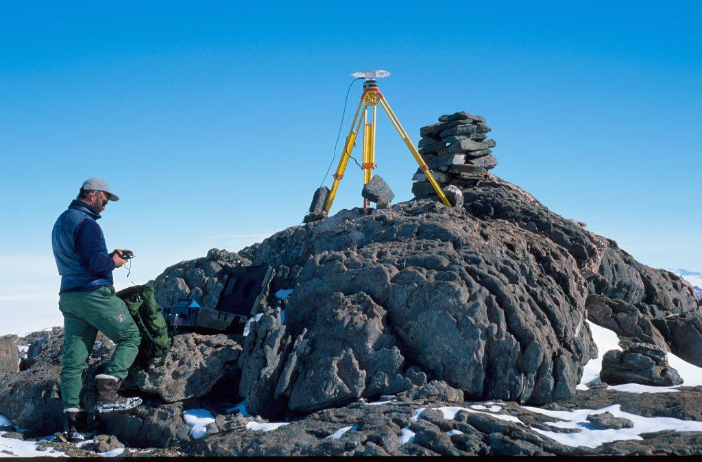 mann står ved en stein med GPS utstyr ved siden av