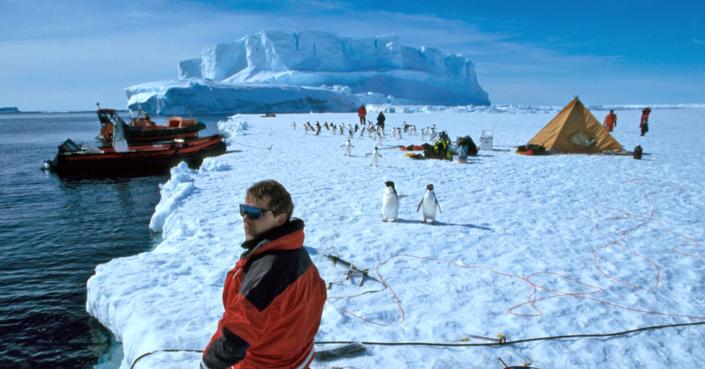 mann, pingvin og utstyr på isflak