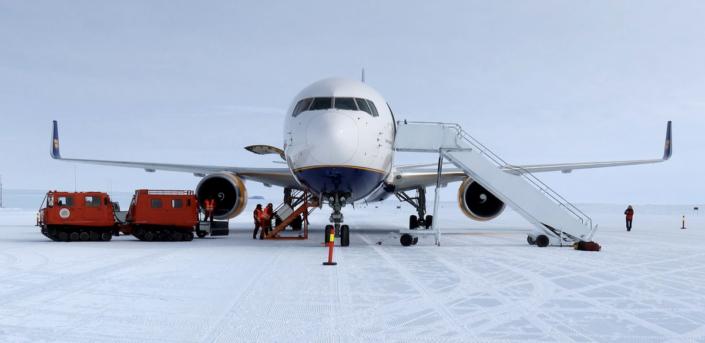 fly på snø med to bandvognser som brukes for å losse av flyet