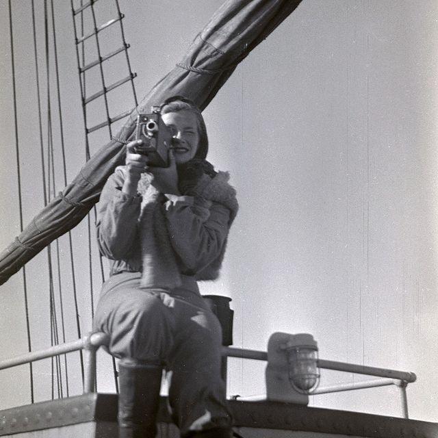 kvinne sitter på rekkverk på skip og titter gjennom et kamera
