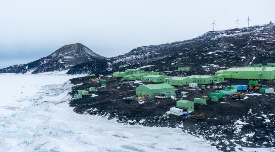 små grønne bygninger ligger på steingrunn i et snedekt landskap
