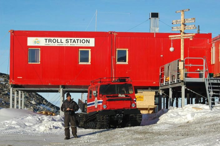 Rød bygning med beltevogn foran